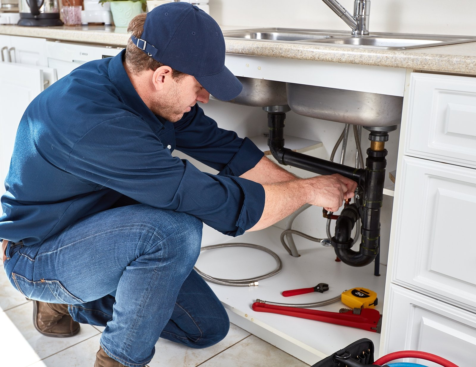 Plumber-in-Dark-Blue-Uniform-Working-on-Kitchen-Sink-Plumbing-Under-Counter